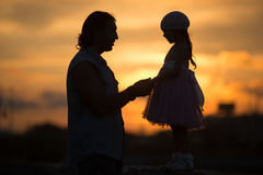 Девушка при папа идя в силуэт захода солнца стоковое изображение rf