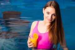 Девушка при питье коктеиля ослабляя на бассейне Стоковые Изображения
