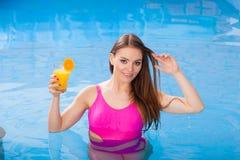 Девушка при питье коктеиля ослабляя на бассейне Стоковое Фото