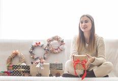 Девушка при подарки рождества сидя на софе Стоковая Фотография