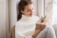 Девушка при подарок рождества сидя дома Стоковая Фотография RF