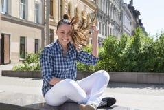 Девушка при порхая волосы сидя на стенде против backgro Стоковые Фото