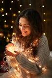 Девушка при пригорошня светов рождества, одетая в белом свитере, темная деревянная предпосылка, концепция зимнего отдыха стоковое фото rf