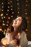 Девушка при пригорошня светов рождества, одетая в белом свитере, темная деревянная предпосылка, концепция зимнего отдыха стоковое изображение rf