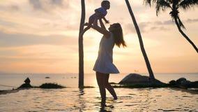 Девушка при ребенок идя и играя на пляже во время захода солнца Отдых семьи акции видеоматериалы