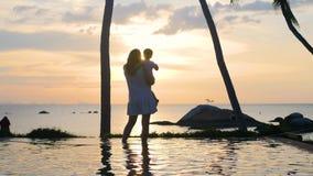Девушка при ребенок идя и играя на пляже во время захода солнца Отдых семьи сток-видео