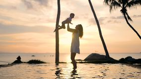 Девушка при ребенок идя и играя на пляже во время захода солнца Отдых семьи видеоматериал