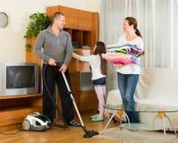 Девушка при родители очищая дома Стоковые Изображения RF