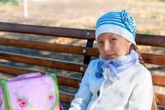Девушка при рюкзак сидя на стенде Стоковое Изображение