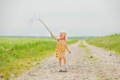Девушка при сеть бабочки имея потеху Стоковое Изображение RF