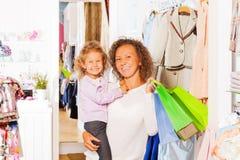 Девушка при счастливая мать держа сумки пока ходящ по магазинам Стоковое Фото