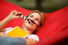 Девушка при тетрадь отдыхая на красном гамаке Стоковое фото RF