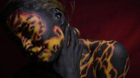 Девушка при фантастическое тело крася в целом тело мистически двигает во время танца на красной предпосылке акции видеоматериалы