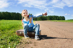Девушка при чемодан стоя о дороге Стоковое Изображение