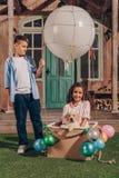 Девушка при щенок labrador сидя в коробке воздушного шара пока мальчик стоя близко мимо Стоковые Фотографии RF