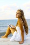 Девушка при smartphone отдыхая на пляже Стоковые Изображения RF