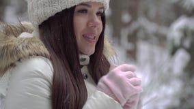 Девушка пробует греть ее руки в девушке леса зимы красивой с длинными темными волосами в белой куртке идя в winte видеоматериал