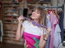 Девушка пробуя на бабочке на предпосылке магазина Красивая женщина в магазине одежды Концепция аксессуаров ходя по магазинам Стоковая Фотография RF