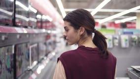 Девушка пропуская через строку экранов ТВ в магазине электроники ища мяукает домашняя электроника акции видеоматериалы