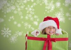 Девушка против серой предпосылки внутри подарочной коробки с шляпой и снежинками рождества Санты Стоковая Фотография