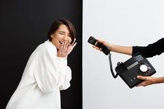 Девушка протягивая к старому телефону подслушивая над черно-белой предпосылкой Стоковое Фото