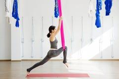 Девушка протягивая ноги с помощью гамака Воздушная йога тренировки Стоковая Фотография RF