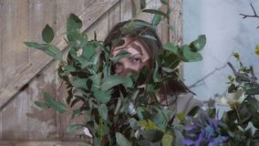 Девушка прячет ее глаза за пуком евкалипта стоковая фотография rf