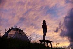 Девушка путешественника смотрит восход солнца, облачное небо с цветами серии стоковые изображения