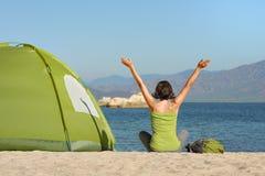 Девушка путешественника с поднятый вверх вручает наслаждаться взглядом на море и moun Стоковые Изображения