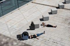 Девушка 2 путешественников лежа на вымощая каменном ожидании и иметь ванны солнца стоковые изображения rf