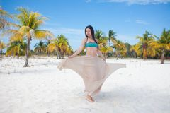 Девушка путешествует к морю и счастлива Молодые привлекательные танцы женщины брюнета развевая ее юбка против тропического ландша стоковое фото