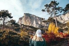 Девушка путешествуя в лесе осени горой Стоковые Фото