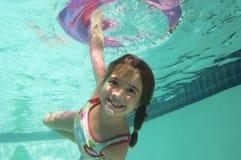 Девушка плавая под водой с раздувным кольцом Стоковое фото RF