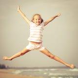 Девушка пляжа скачки летания на голубом береге моря стоковая фотография rf