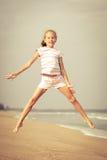 Девушка пляжа скачки летания на голубом береге моря стоковое изображение rf