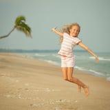 Девушка пляжа скачки летания на голубом береге моря стоковые фотографии rf