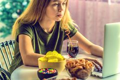 Девушка работает на компьютере и ест фаст-фуд стоковое фото