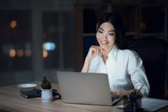 Девушка работает поздно в темном офисе с компьтер-книжкой Молодая красивая девушка коммерсантки в офисе Стоковые Изображения