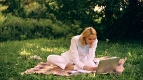Девушка работает при компьтер-книжка сидя на одеяле в парке Молодая женщина с компьтер-книжкой изучая outdoors сток-видео