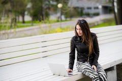 Девушка работает при портативный компьютер сидя на стенде в парке смотря к камере и усмехаться Стоковая Фотография RF