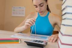 Девушка работает с атласом на деревянной таблице Концепция образования - книги на столе Стоковая Фотография RF