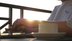 Девушка работает с компьтер-книжкой и чашкой кофе на таблице на заходе солнца в солнце акции видеоматериалы