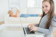 Девушка работая на компьтер-книжке и ее мать читая газету Стоковые Фото