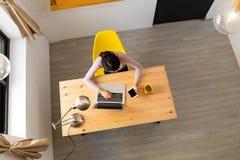 Девушка работая на компьтер-книжке и мобильном телефоне дома Стоковое Фото
