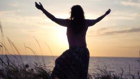 Девушка радуется море, солнце и заход солнца, повышения ее руки вверх, водовороты HD Стоковые Изображения RF
