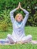 Девушка размышляет на предпосылке природы луга зеленой травы половика Раздумье женщины ослабляя практикуя Раздумье изо дня в день стоковая фотография