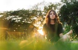 Девушка размышляет на траве на заходе солнца Стоковые Изображения