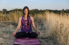 Девушка размышляя на циновке йоги с крупным планом глаз Стоковое Фото
