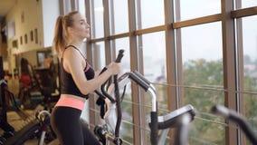 Девушка разрабатывая с имитатором и смотря вне окно в спортзале 4K акции видеоматериалы
