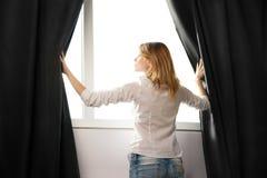Девушка раскрывает занавесы и ослаблять в утре Стоковое фото RF